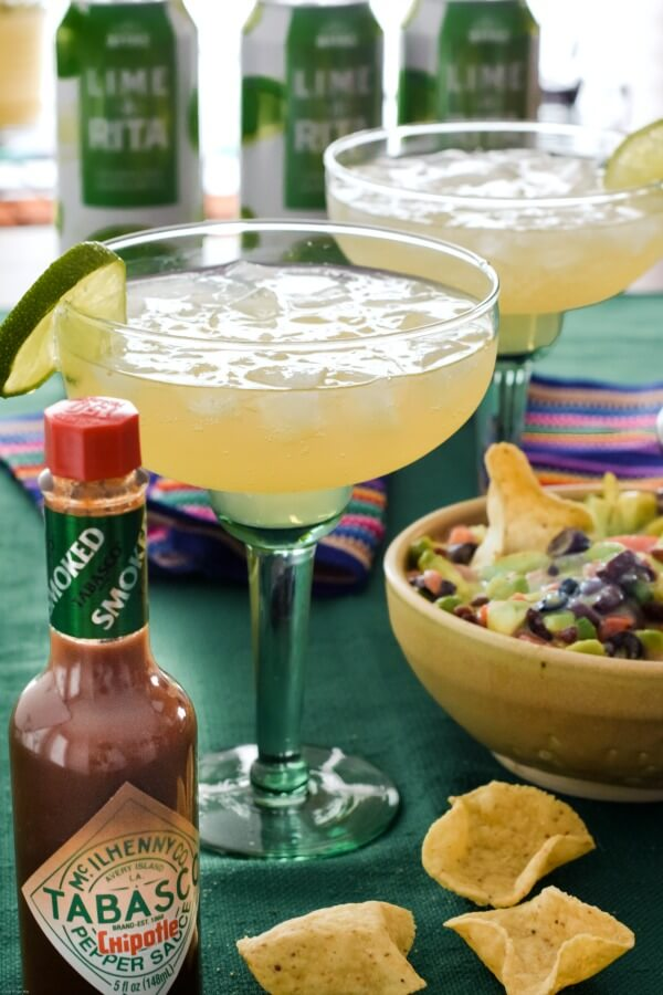 Two green margarita glasses filled with Lime-A-Ritas over ice with avocado salsa in a tan pottery bowl with a bottle of TABASCO® Chipotle Sauce next to the drinks.