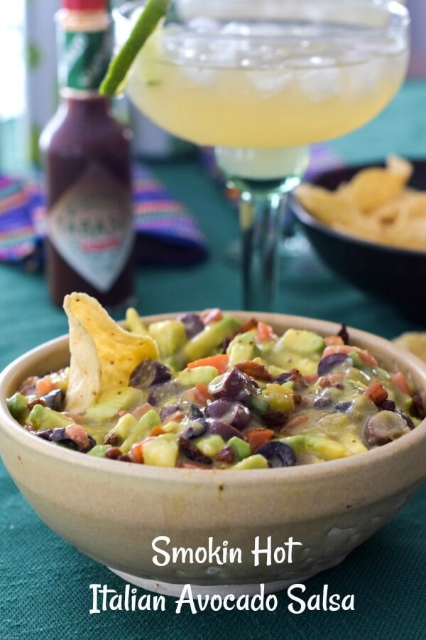 Close up of a tan pottery bowl tilled with Italian avocado salsa a mixture of avocados, diced tomatoes, black olives, and a tortilla chip stuck in the salsa, with a bottle of TABASCO® Chipotle Sauce in the background and a green margarita glass filled with Lime-A-Rita drink.