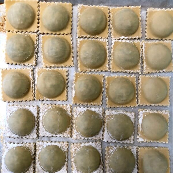 A parchment lined baking sheet filled with rows of lamb ravioli.