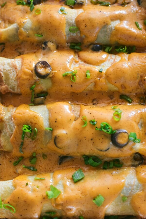 Close up cheese sauce covered beef enchiladas lined up in a aluminum casserole pan.