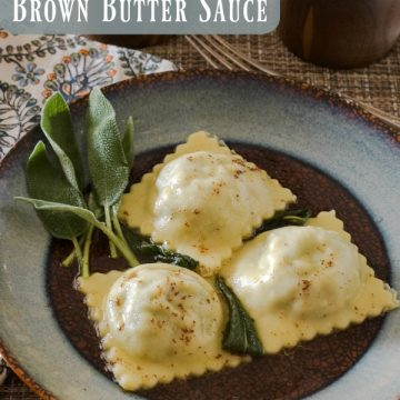 Three lamb ravioli on a blue and brown round plate with a sprig of sage on the side. A multi-color napkin is under the plate.