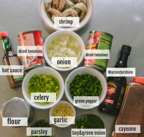 The ingredients for Shrimp Creole are all prepared and on a stainless steel table.