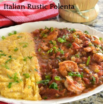 White bowl holds polenta and shrimp creole in tomato sauce with a red striped tea towel and a bottle of chianti wine.