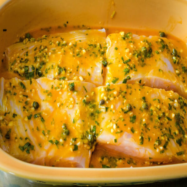 Four halibut fillets marinating in a herb citrus marinade in a gold glass casserole.