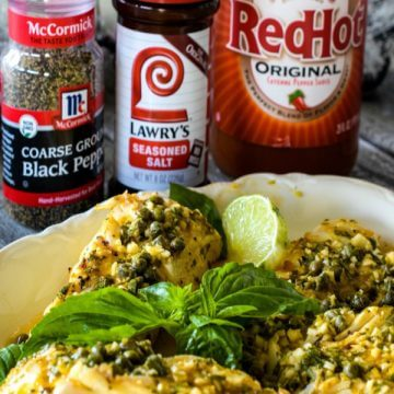 Four Grilled Halibut fillets on a white plate with McCormick® Black Pepper, Lawrey's® Seasoned Salt, and Frank's®RedHot Sauce