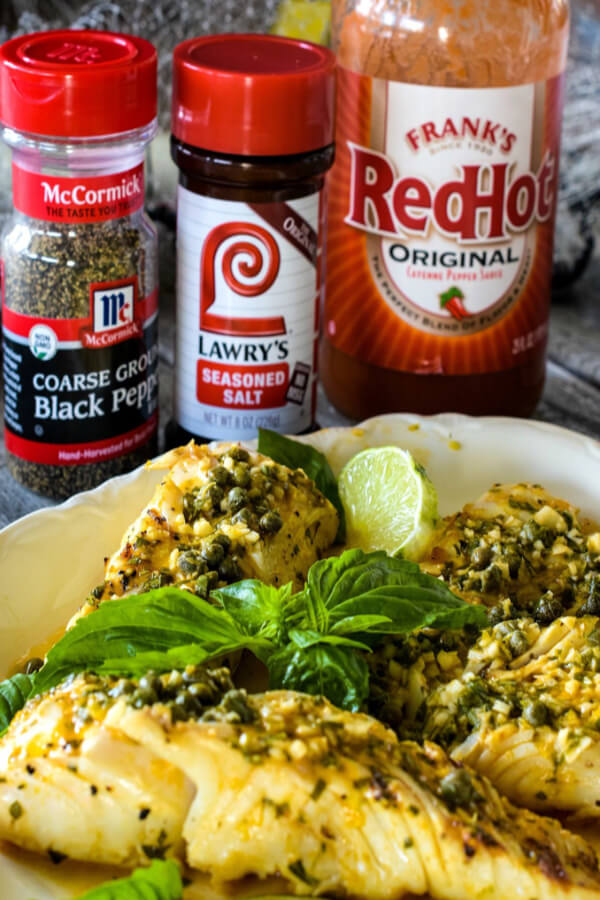 Four Grilled Halibut fillets on a white plate with McCormick® Black Pepper, Lawry's® Seasoned Salt, and Frank's®RedHot® Sauce