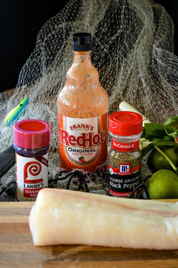 Raw halibut fillets on wood cutting board. A fishing net with a fishing lure and bobber in the net. Seasoned salt, hot sauce, and black pepper with a lime behind the fish.