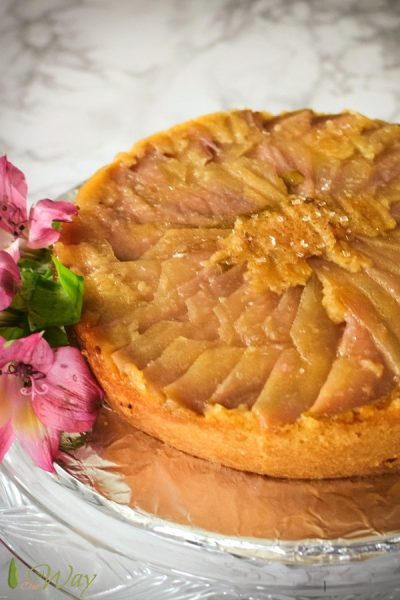 Golden pear round upside down cake with fuchsia lilies on the side of the cake plate.