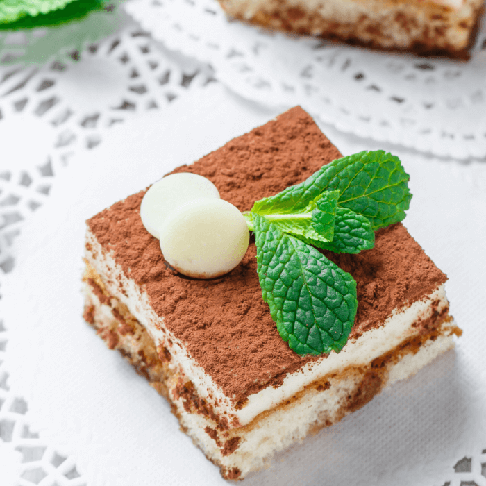 A mini cake with cocoa on top of the tiramisu square.