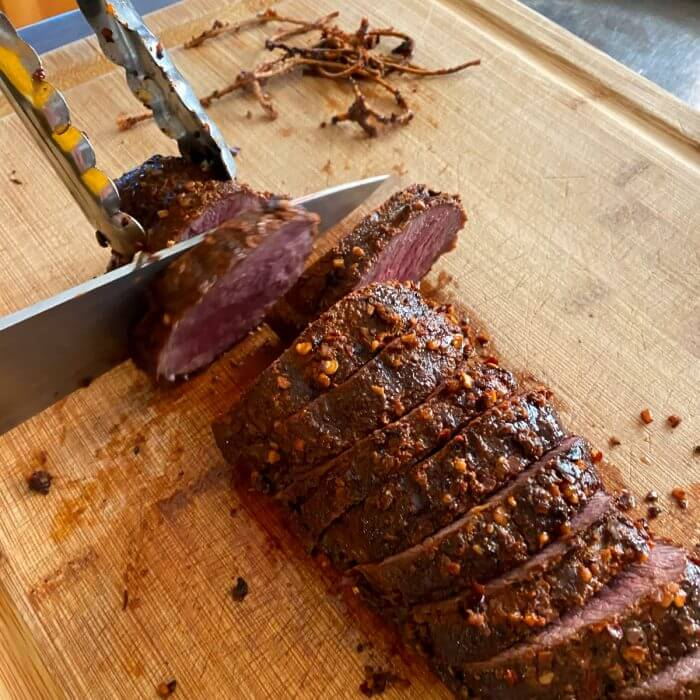 Venison Backstrap on cutting board being sliced.