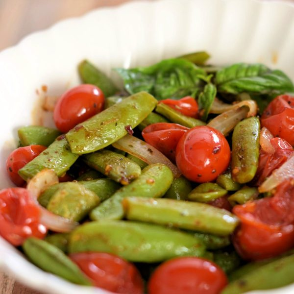 Roasted Sugar Snap Peas with Grape Tomatoes in a white bowl.