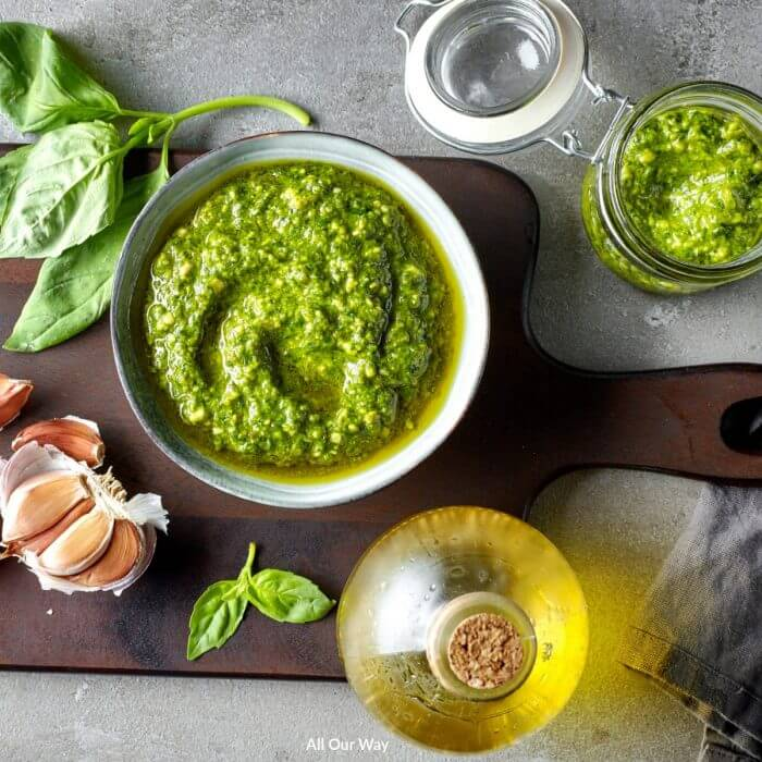 Green basil pesto in bowl with olive oil and garlic cloves on a wooden cutting board.