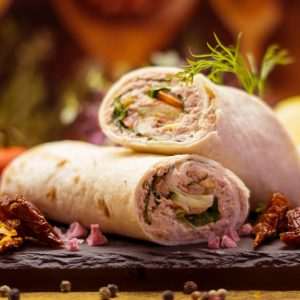 Two tuna salad wraps with peppers and dill.