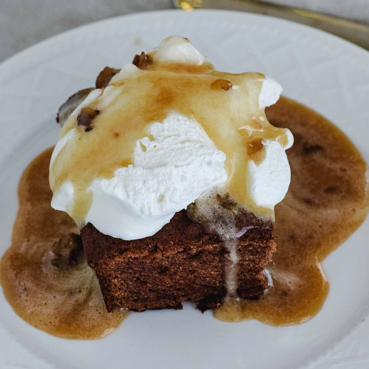 Persimmon pudding with whipped cream and a caramel pecan sauce over it