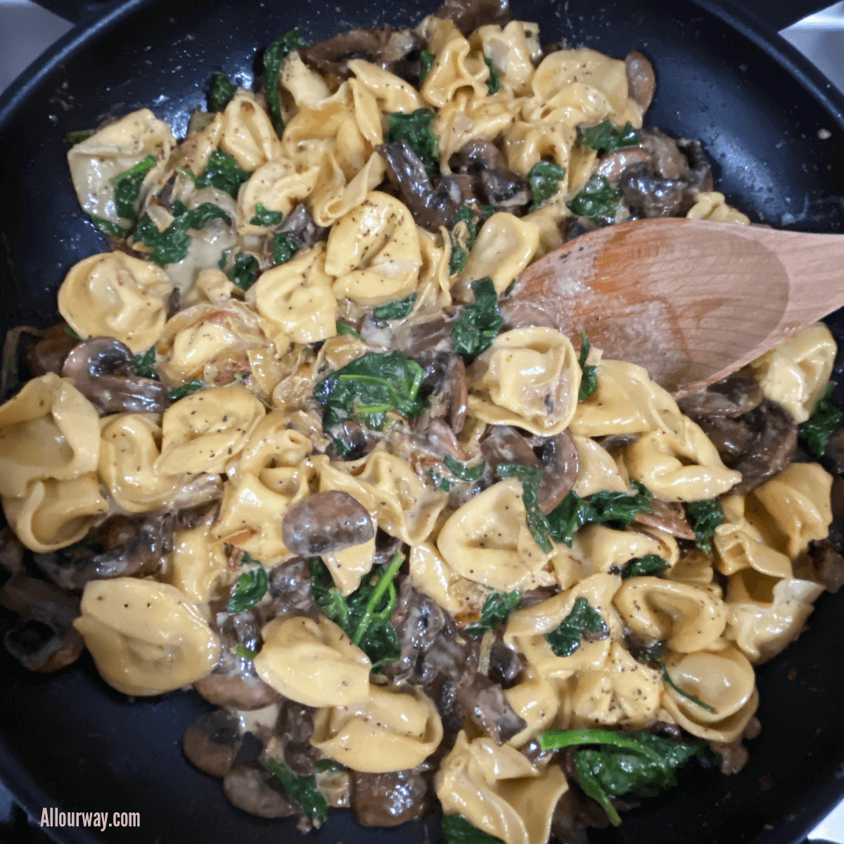 Skillet with wooden spoon stirring the saucy cheese tortellini with spinach, mushrooms and caramelized onions