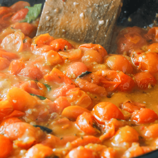 Fresh Cherry Tomato Sauce with Basil in a Black Cast Iron Skillet with wooden spoon.