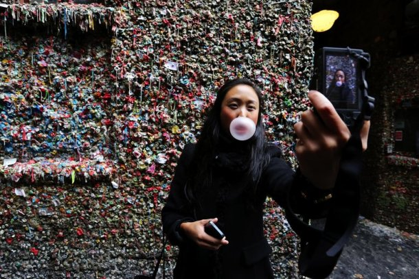 Silvia Lim CQ, visiting from Sweden, takes a self-portrait at the Gum Wall attraction in Post Alley. (Alan Berner/The Seattle Times)