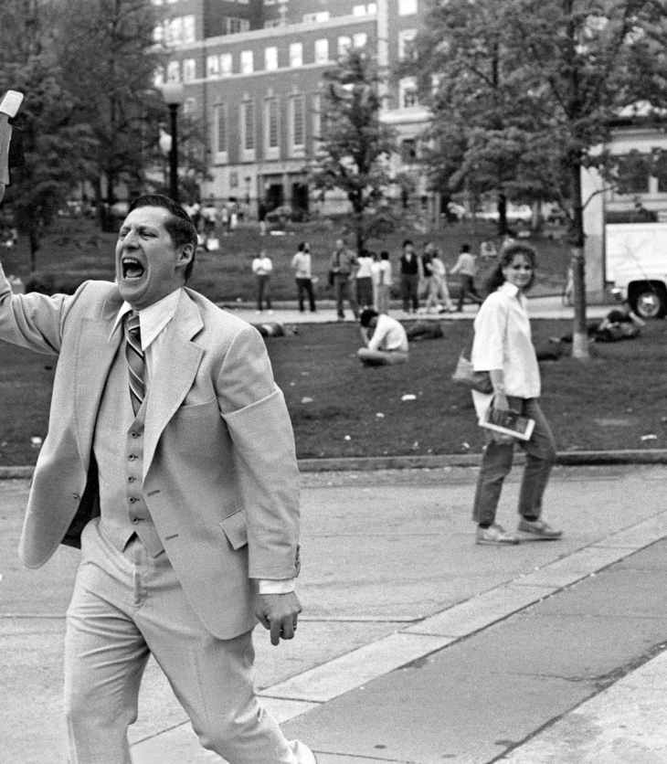 man in white suit standing on street