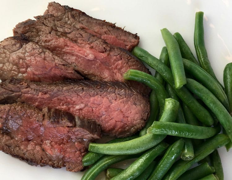 steak and green beans on white plate