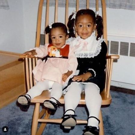 Erinn Westbrook and her cousin sister sitting on the chair.