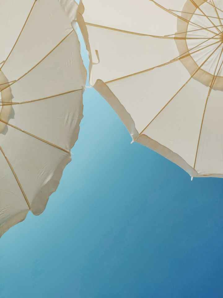 Two nude pool umbrellas