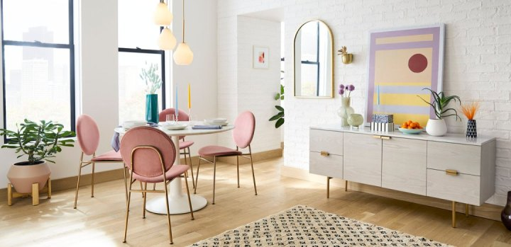 Mid century modern dining room with a marble table, and pink suede chairs with gold accents