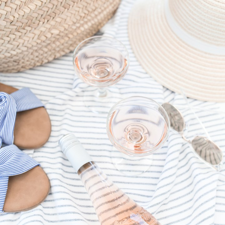 Wine glasses at beach with beach hat, flip flops and sunglasses, on a blanket