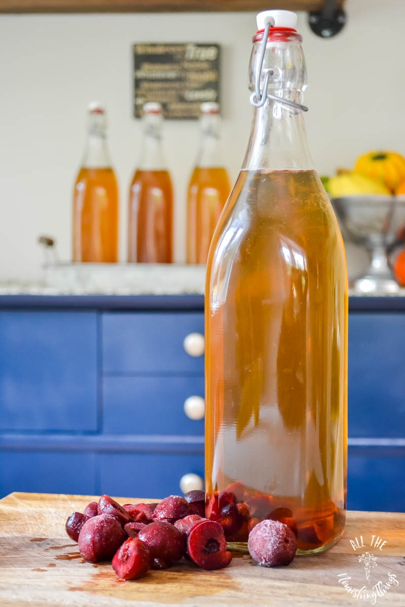 bottle of kombucha with sliced cherries