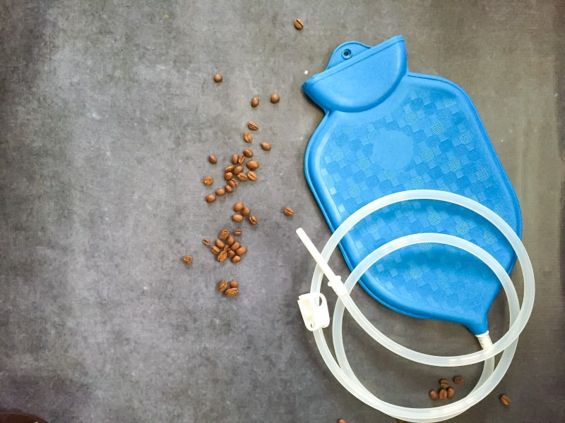 blue enema bag with coffee beans on grey background