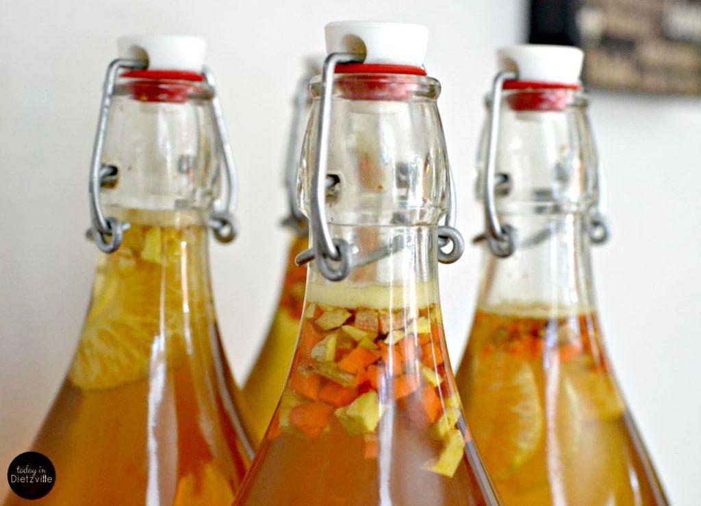 ginger and turmeric kombucha in glass swing-top bottles
