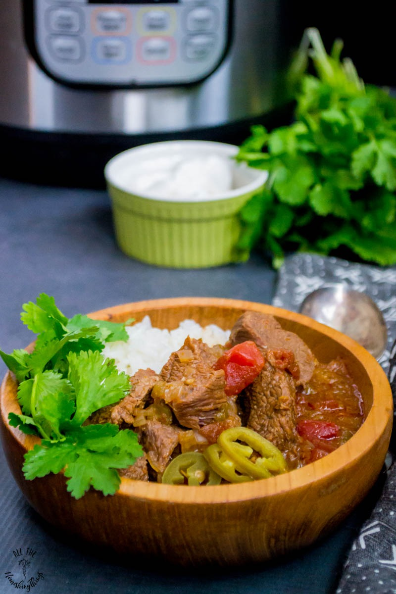 instant pot mexican beef stew in wooden bowl with an instant pot in the background