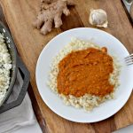 instant pot chicken tikka masala on white plate with wooden cutting board and cast iron skillet of rice
