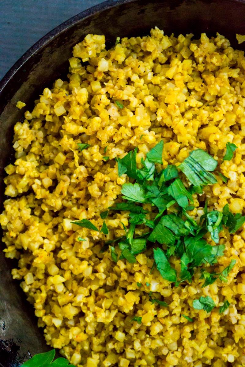 close-up image of yellow turmeric cauliflower rice with parsley garnish