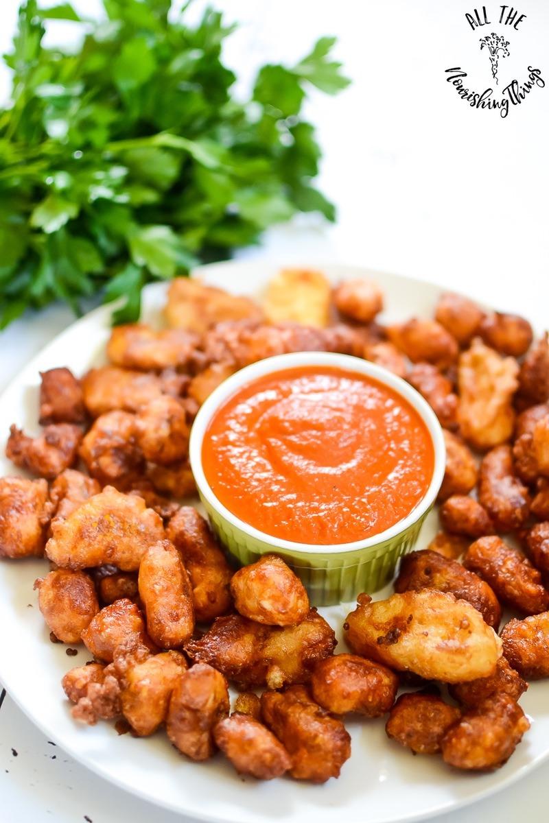 white platter of fried cheese curds with green ramekin of marinara