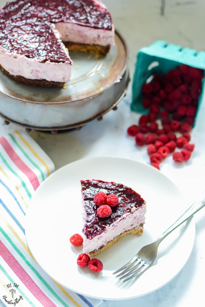 slice of keto no-bake raspberry cheesecake with the whole cheesecake in background with fresh raspberries