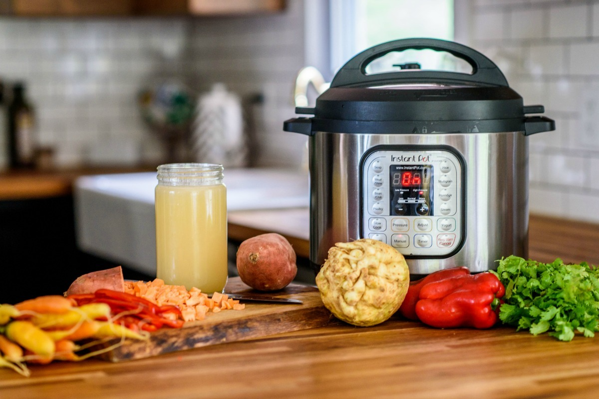 instant pot on counter surrounded by colorful vegetables and jar of bone broth