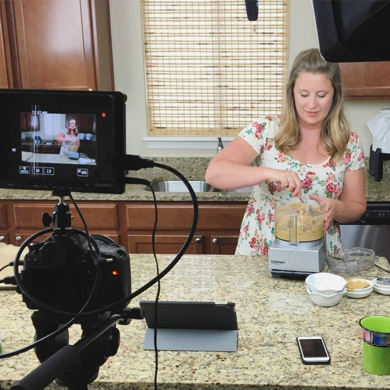 woman in floral shirt cooking in front of a camera