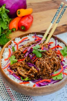 Asian pulled pork in a wooden bowl with chopsticks. Peppers and veggies on a wooden cutting board in background.