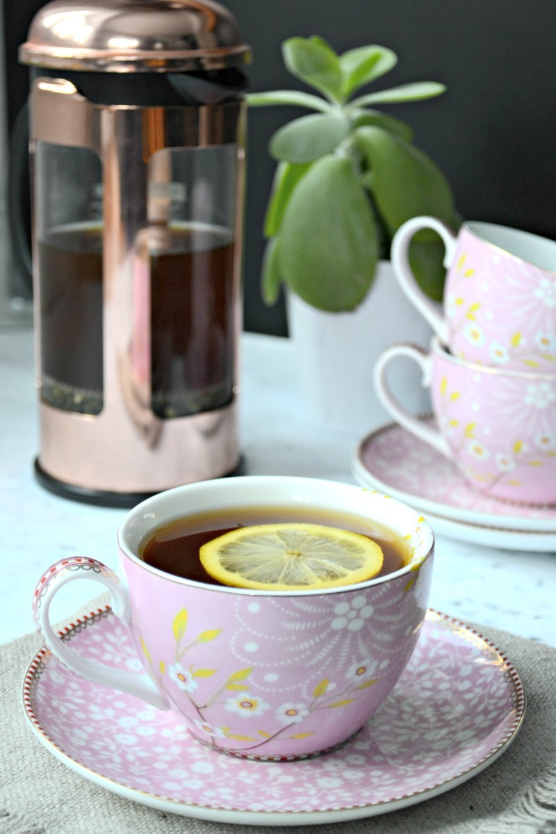 pink tea cup full of tea with lemon and a french press with extra teacups in the background