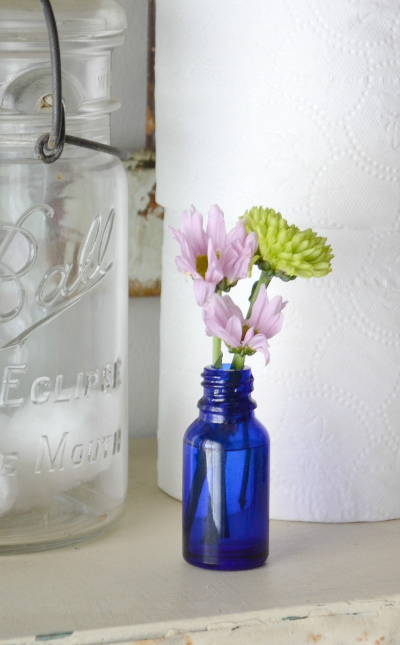 cobalt blue bottle with purple and green flowers next to toilet paper