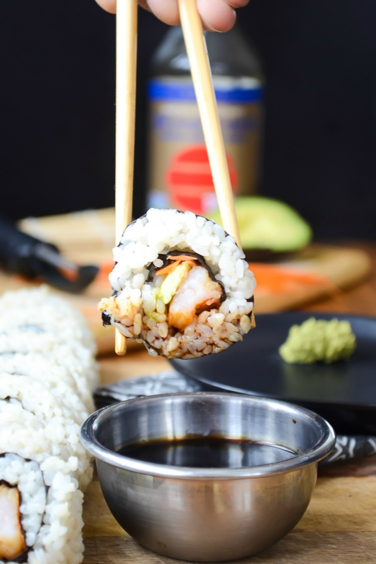 instant pot sushi rice sushi roll held by chopsticks above silver bowl of soy sauce