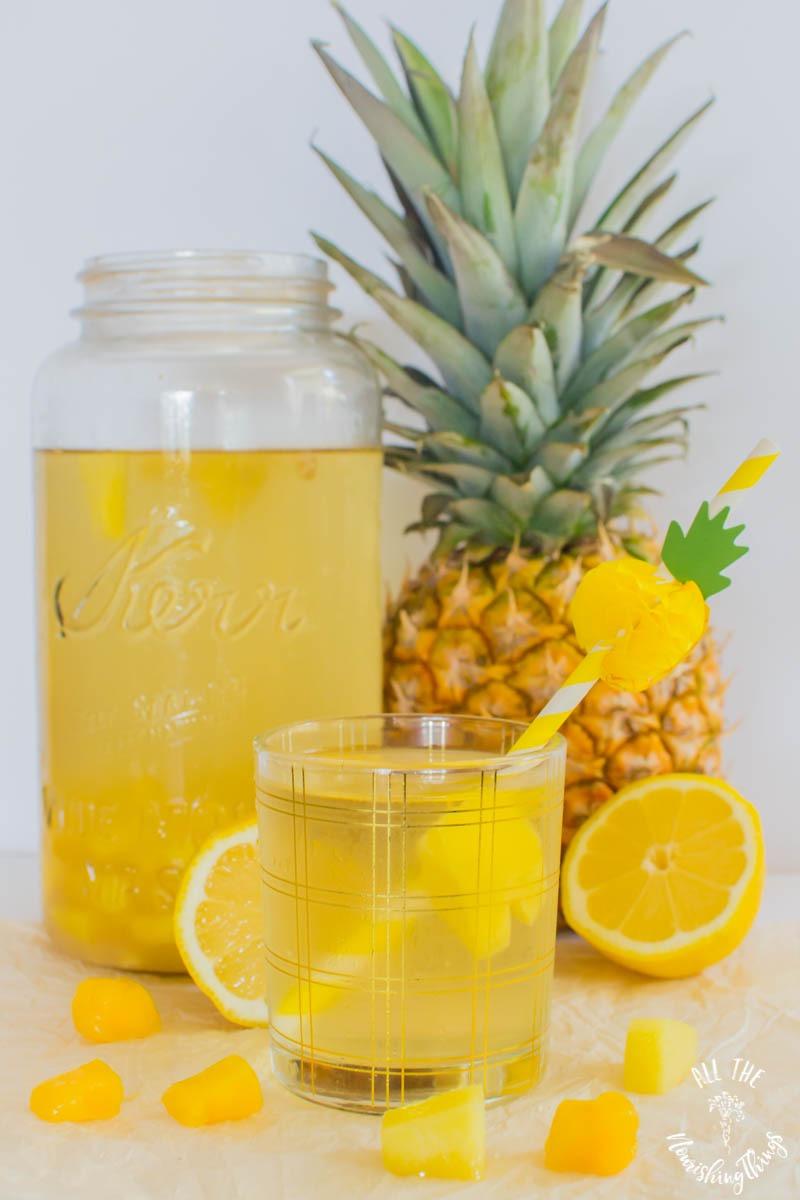 pineapple mango switchel with pineapple straw and lemons