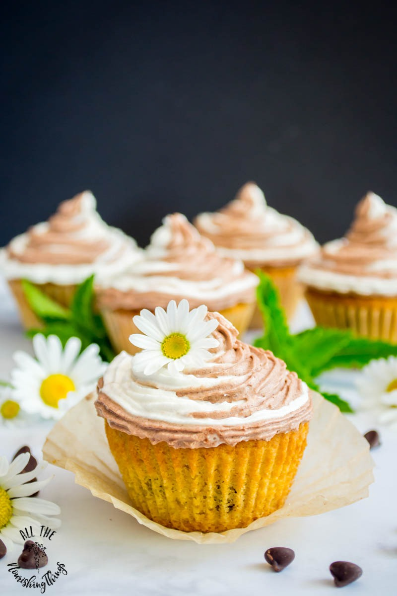 keto chocolate chip cupcakes garnished with daisy on black background