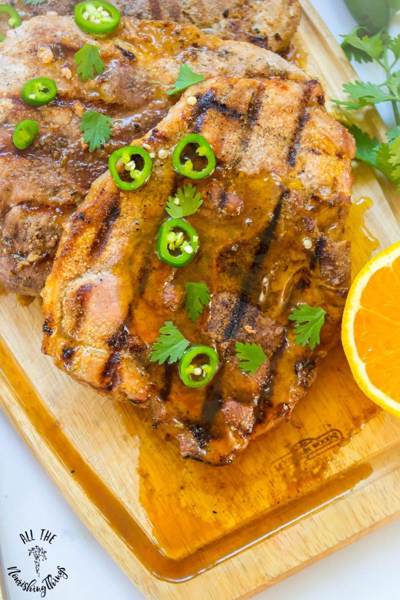 paleo grilled pork chops with orange-ginger-jalapeno glaze on wooden cutting board