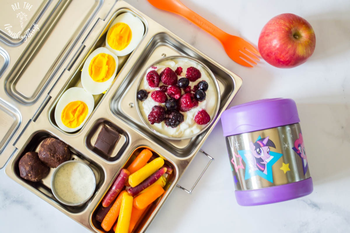 planetbox bento box with yogurt and berries and boiled eggs and carrots