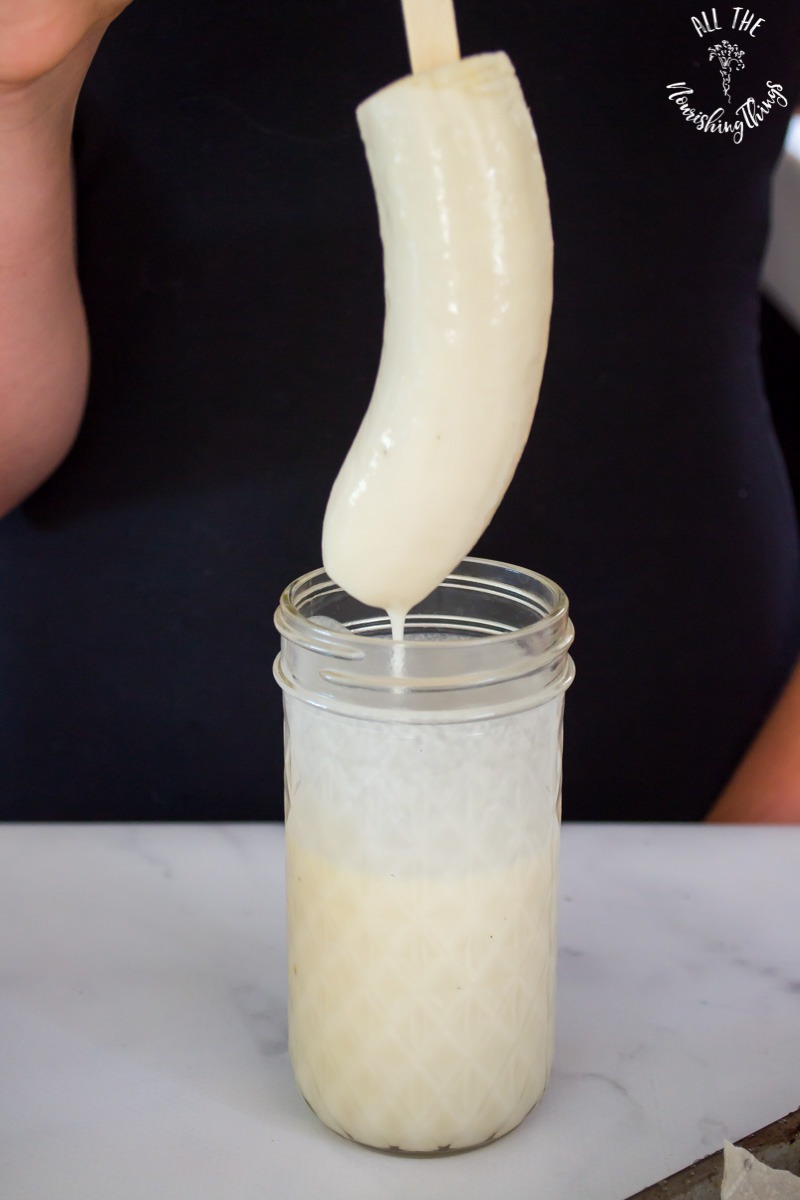 dipping banana into jar of coconut butter to make banana ghosts