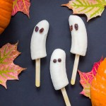 3 banana ghosts on black background with fall leaves and pumpkins