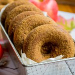 horizontal image of soaked gluten-free apple cider donuts in metal baking tin