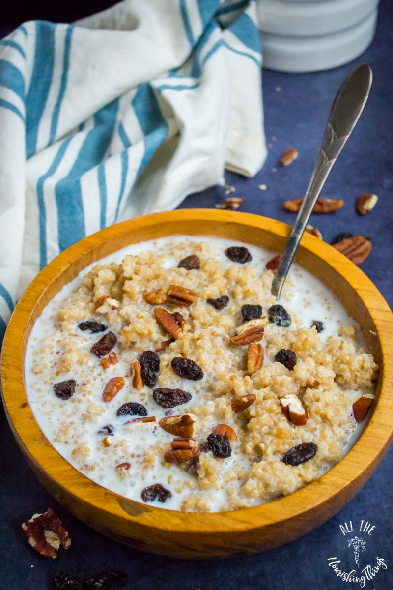 wooden bowl with soaked instant pot quinoa breakfast porridge with a spoon in the bowl and a blue striped towel in the background