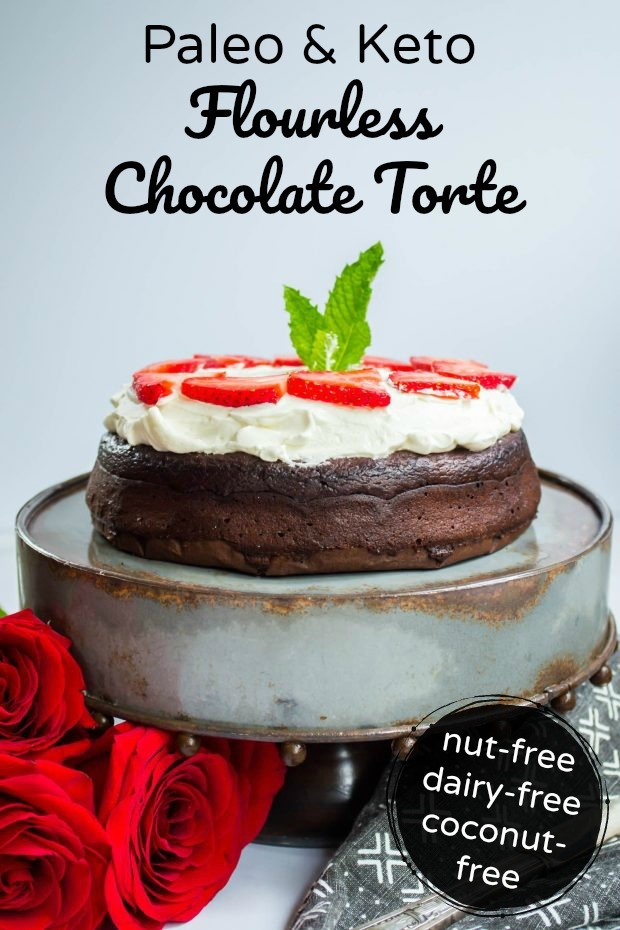 paleo and keto flourless chocolate torte on a metal cake stand topped with whipped cream and strawberries with text overlay above the torte